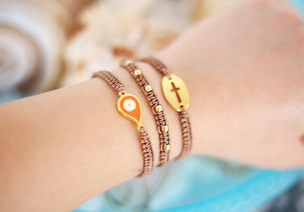 woman hand wearing stylish brown bracelets with evil eye and cross - macrame bracelets - greek jewelry