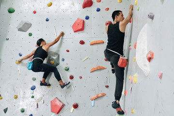 Sporty couple enjoying bouldering in climbing center