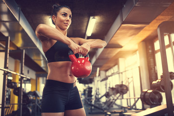 Female use kettle bell weight for exercising muscles