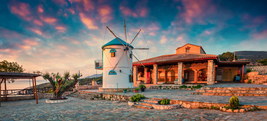 Picturesque morning scene of the countryside with windmill. Colorful spring sunrise on the Zakynthos island, Korithi location, Ionian Sea, Greece, Europe. Beauty of countryside concept background.