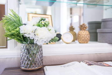 white flower with glass vase on reading table