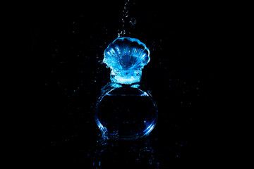 water splash drop with glass bottle of cosmetic perfume smell luxury on black background