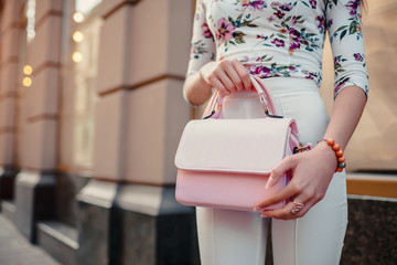 Close-up of stylish female handbag. Young woman wearing beautiful outfit and accessories outdoors.