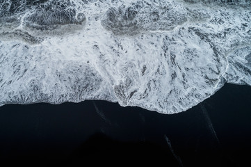 Aerial view of Black sand beach and ocean waves in Iceland.