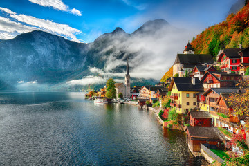 Foggy autumnal sunrise at famous Hallstatt lakeside town reflecting in Hallstattersee lake