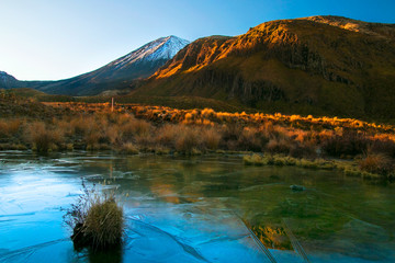 Early morning sunrise, landscape scenery of frozen blue pure water lake, wild mountains and huge volcano with the peak covered by first snow, autumn colours and golden sun rays, New Zealand nature