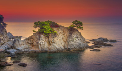 Sea landscape at sunrise. Beautiful view of cliff in Mediterranean at dawn in morning. Bright red sky over Spanish coast of Lloret de Mar, Costa Brava, Spain. Amazing nature and coastline with rocks.