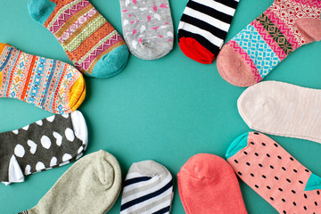 Many socks are piled in a circle. View from above. Many multicolored socks are made in the shape of a circle or sun. There is space for text. Clothes made of knitwear.
