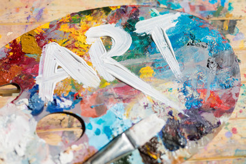 Word art painted with white gouache on colorful palette with paintbrush near by