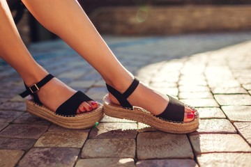 Stylish woman wearing black summer shoes with straw sole outdoors. Comfortable sandals. Beauty fashion.