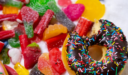 Mix of tempting sweet cakes, donuts and candy with sugar spread in unhealthy nutrition, chocolate abuse and sugar addiction concept, body and dental care and health problems..