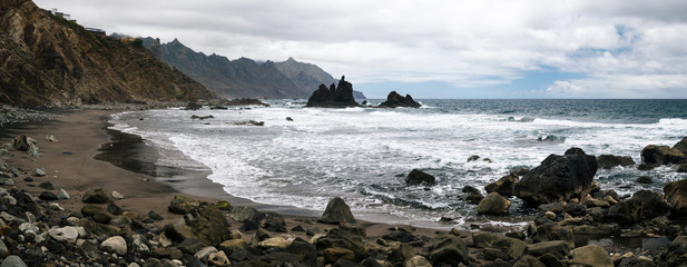Panoramic view of Benijo beach with big waves, black sand and rocks on the north coast of the island Tenerife, Spain