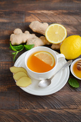 Ginger root tea with lemon and honey on wooden background, selective focus, copy space.