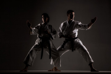 karate dziewczyna i chłopak pozowanie na ciemnym tle