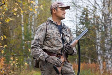 hunter with gun in the birch forest