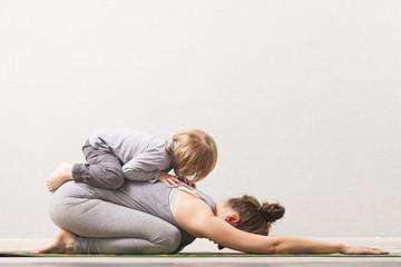 kobieta mama ćwiczy jogę z dzieckiem