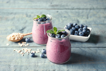 Tasty blueberry smoothie in jars, berries and oatmeal on wooden table