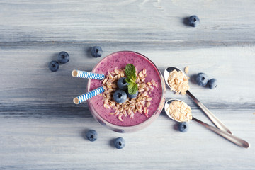 Tasty blueberry smoothie in glass, berries and oatmeal on wooden table, top view