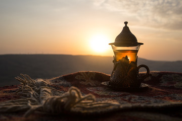 Arabian tea in glass on a eastern carpet. Eastern tea concept. Armudu traditional cup. Sunset background. Selective focus