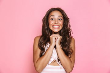 Image of pleased woman 20s with long hair wearing dress laughing and holding fists together, isolated over pink background