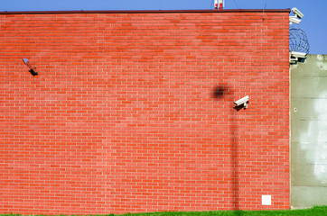 Wall of red brick with installed cameras for observation
