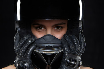 Beautiful young woman in black leather gloves and protective motorbike helmet in studio. Attractive self determined female motocycle racer wearing hands and body protection from falls and accidents