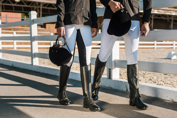 cropped image of equestrians in professional apparel walking near fence and holding riding helmets at ranch