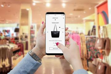 Dziewczyna w butiku szuka torebki na smartfonie, aby kupić online