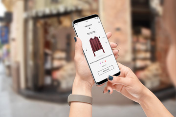 Girl in front of clothing store searching for hoodie online on her smartphone