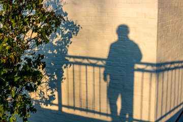 The shadow of a man on a white building wall