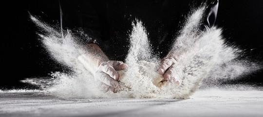 Flour flying into air as chef slams dough on table