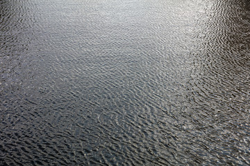 City river water background in the afternoon with rippled dark surface