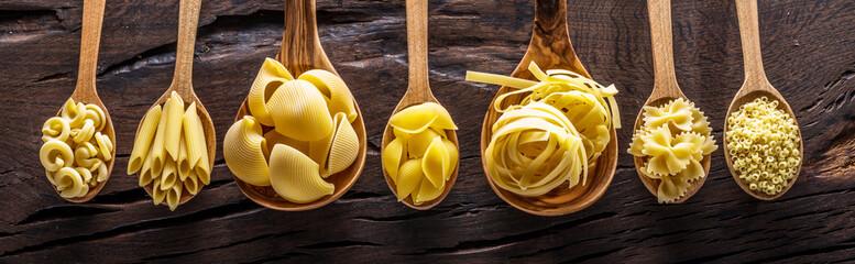 Różne rodzaje makaronów w drewniane łyżki na stole. Widok z góry.