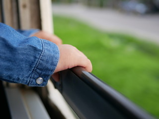 Close up of little baby's hands holding on a frame of an opened window on a traveling train - travel helps the babies become adaptable and more flexible
