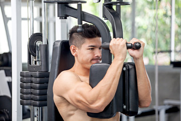 Muscular bodybuilder guy doing Heavy Weight Exercise For Chest In The Gym .sport young fitness man training with Butterfly Exercise Machine