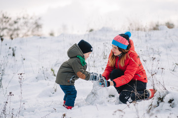 Mother and little toddler boy walking in the winter forest and having fun with snow. Family enjoying winter. Child and mom watching falling snow outdoors. Winter lifestyle concept.
