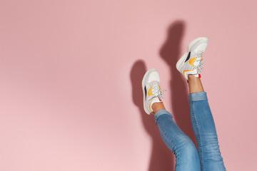 Kobieta w eleganckich sneakers blisko kolor ściany, zbliżenie. Miejsce na tekst