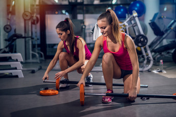 Two sporty girls in a gym preparing theirs equipment for training.