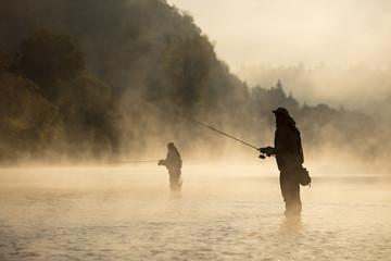 Mężczyźni łowiąc w rzece z muchą w lecie.