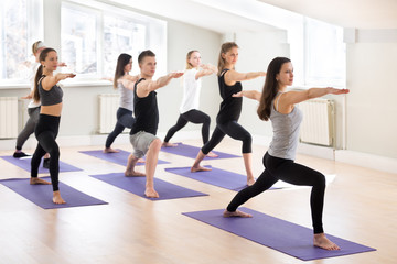 Group of young sporty people practicing yoga with instructor, doing Warrior two exercise, Virabhadrasana II pose, working out, indoor, students training in club, studio full length. Well-being concept