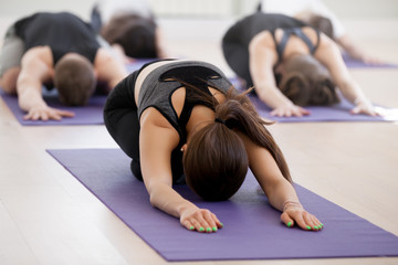 Group of young sporty people practicing yoga lesson with instructor, doing Child exercise, Balasana pose, working out, indoor, students training in club, studio close up. Well-being concept