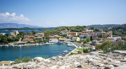 View on the city with colorful houses near the bright blue sea in the background of green mountains in Kassiopi in Corfu island Greece