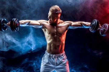 Handsome bodybuilder doing Exercise for the shoulder muscles, deltoid with dumbbell. Studio shot. Smoke.