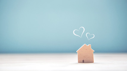 Home sweet home, house wood with heart shape on wooden and blue background, copy space.