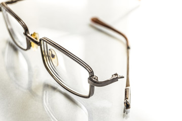 Eyeglasses with a broken shackle on a bright background. Limited depth of field.