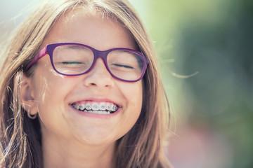 Portret szczęśliwa uśmiechnięta nastoletnia dziewczyna z stomatologicznymi brasami i szkłami
