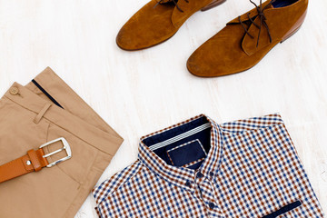 Beige pants, plaid shirt, brown suede shoes and leather belt. Overhead view of men's casual outfit on white wooden background. Flat lay, top view.