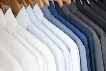 Office Business shirts hanging in a closet ordered by colour