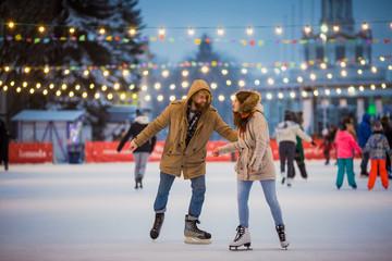Młoda para zakochanych Kaukaski mężczyzna z blond włosami z długimi włosami i brodą i piękną kobietą bawią się, aktywnie jeżdżą na łyżwach na scenie lodowej na rynku zimą w Wigilię