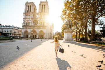 Morning view on the famous Notre-Dame cathedral with woman running on the square dispersing pigeons in Paris, France